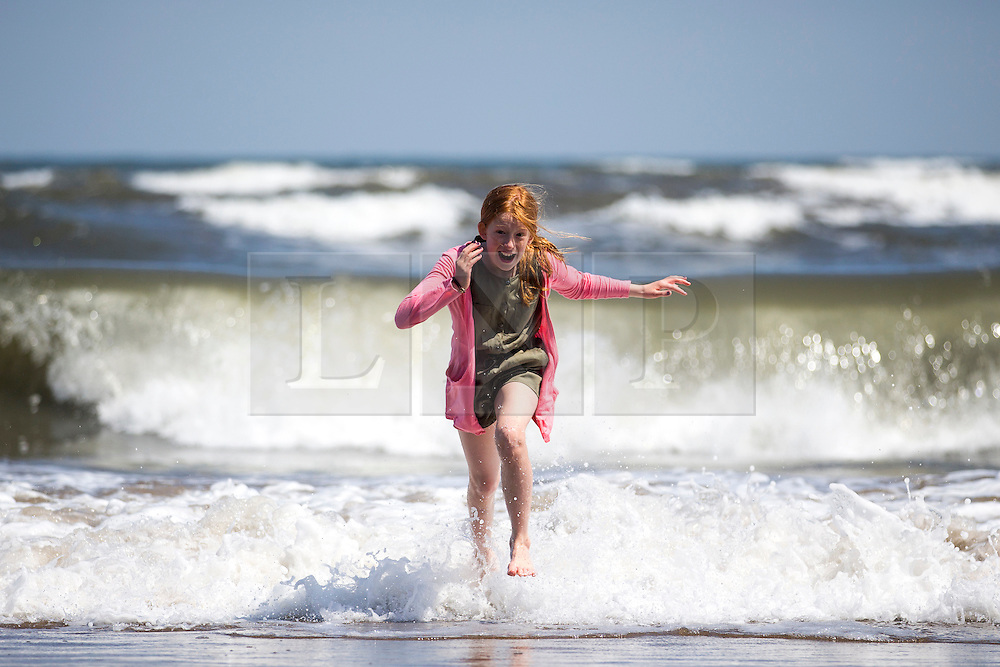 © Licensed to London News Pictures. 05/06/2016. Scarborough UK. 10 year old Cerys run's out of the sea at Scarborough beach on another sunny day in Yorkshire. Photo credit: Andrew McCaren/LNP