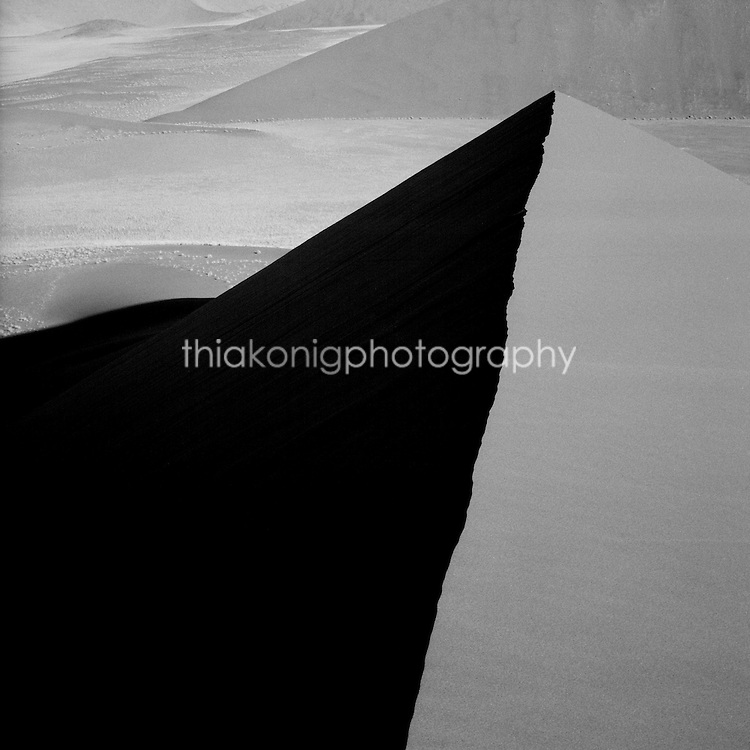 Looking across to the dark side of the dune, the side lighting casts a stark shadow on a dune at Sossusvlei in the Namib desert, Namibia, Africa.