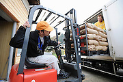 Master sake brewer Philip Harper from the United Kingdom and an unidentified brewery hand unload sacks of rice from a truck at the Tamagawa Sake Brewery in Kyoto, Japan. More than 1,200 sake breweries exist in Japan, though falling domestic consumption has lead some to look to  overseas markets. Photographer: Robert Gilhooly