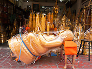 "05 JULY 2011 - BANGKOK, THAILAND:  A Buddha statue laid back for sale on Bamrung Muang Street in Bangkok. Thanon Bamrung Muang (Thanon is Thai for Road or Street) is Bangkok's ""Street of Many Buddhas."" Like many ancient cities, Bangkok was once a city of artisan's neighborhoods and Bamrung Muang Road, near Bangkok's present day city hall, was once the street where all the country's Buddha statues were made. Now they made in factories on the edge of Bangkok, but Bamrung Muang Road is still where the statues are sold. Once an elephant trail, it was one of the first streets paved in Bangkok, it is the largest center of Buddhist supplies in Thailand. Not just statues but also monk's robes, candles, alms bowls, and pre-configured alms baskets are for sale along both sides of the street.         PHOTO BY JACK KURTZ"