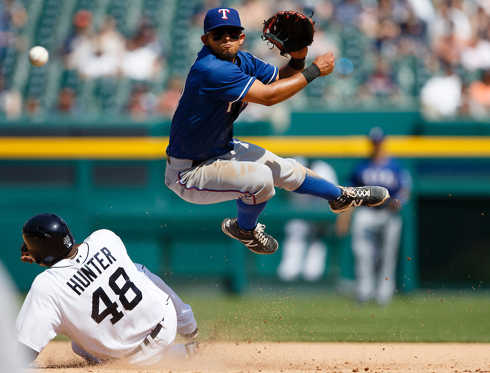 May 25, 2014; Detroit, MI, USA; Texas Rangers second baseman Rougned Odor (73) leaps in the air as he makes a throw to first in an attempted double play as Detroit Tigers right fielder Torii Hunter (48) slides into second during the seventh oating at Comerica Park. Mandatory Credit: Rick Osentoski-USA TODAY Sports