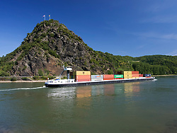 Barge carrying containers passing famous Loreley rock on the River Rhine in Germany