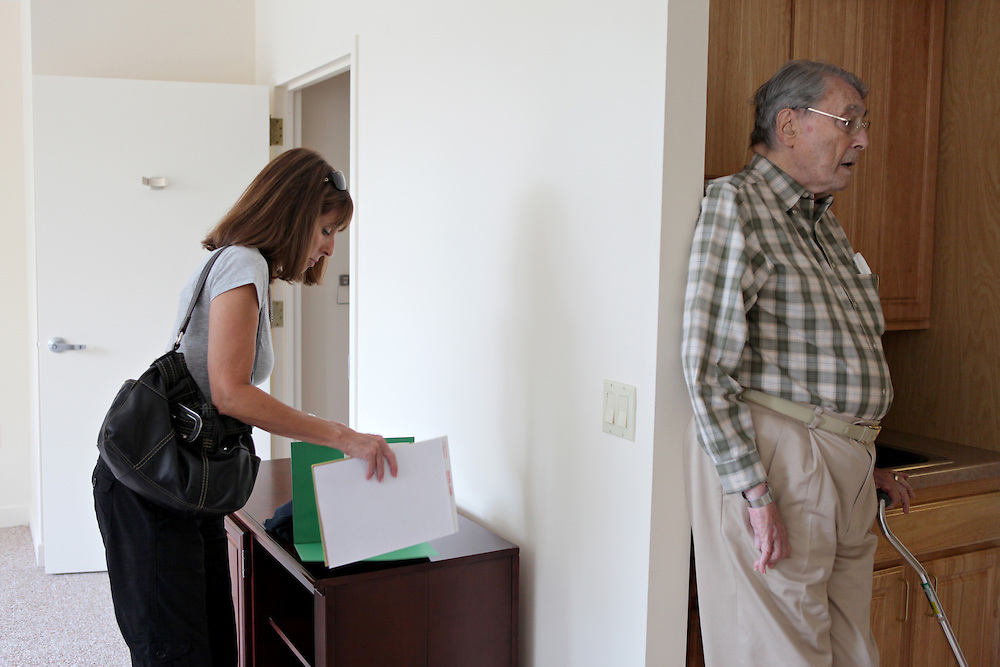 Xavier Mascareñas/The Journal News; Gilda, left, shuffles through paperwork required for residence at the Towers while her father, Ben, waits in a different part of the unit his daughter is considering.