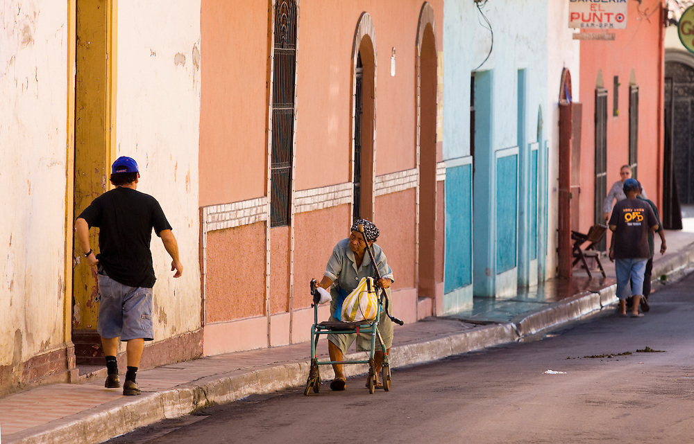 An elderly and  disabled woman walks slowly up the street, past pedestrians in the Nicaraguan town of Granada. She is supported by a walking frame.
