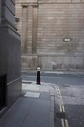 Landscape of a lone traffic bollard on the corner of Lothbury and Tokenhouse Yard, two narrow and historic streets with the high walls of the Bank of England in the background - in the City of London, the capital's financial district. The area was populated with coppersmiths in the Middle Ages before later becoming home to a number of merchants and bankers. Lothbury borders the Bank of England on the building's northern side. Tokenhouse St dates from Charles I and was where farthing tokens were coined. The City of London is the capital's historic centre first occupied by the Romans then expanded during following centuries until today, it has a resident population of under 10,000 but a daily working population of 311,000.