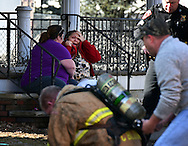 A woman cries on a neighbors porch while watching as firemen extinguish a fire at her homeon February 22 2016.