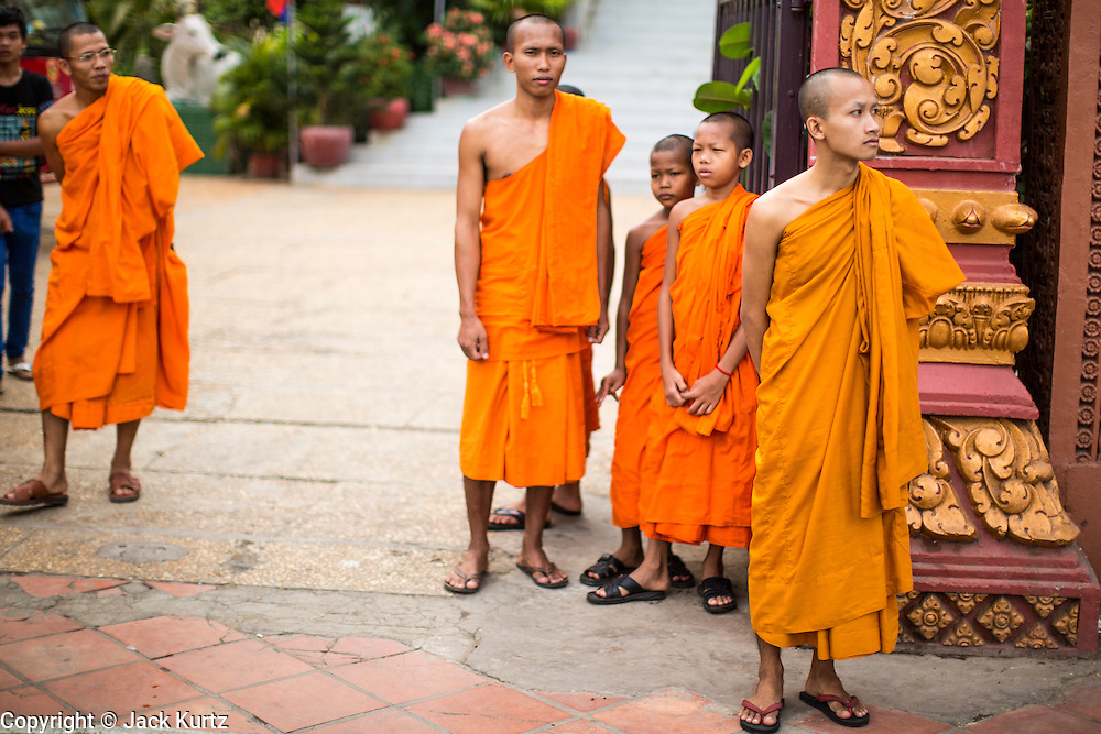 02 FEBRUARY 2013 - PHNOM PENH, CAMBODIA:  Buddhist monks in front of Wat Ounalom in Phnom Penh. Wat Ounalom (also Wat Onalaom and several other spellings) is a wat located on Sisowath Quay in Phnom Penh, Cambodia, near the Royal Palace of Cambodia. It is the most important wat in Phnom Penh, and the center of Cambodian Buddhism. It was established in 1443 and consists of 44 structures. The temple complex was damaged during the Khmer Rouge but has since been restored. The main complex has a stupa which contains what is believed to be an eyebrow hair of Buddha and an inscription in Pali.      PHOTO BY JACK KURTZ