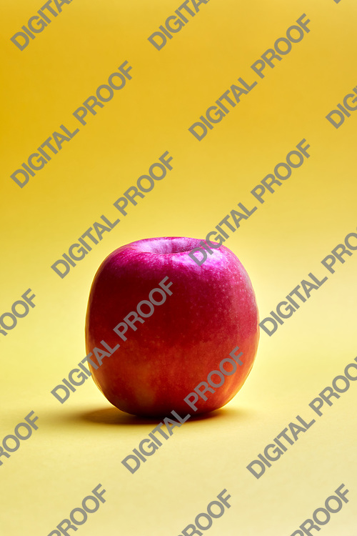 Close-up shot of fresh red apple lying on bright yellow background.