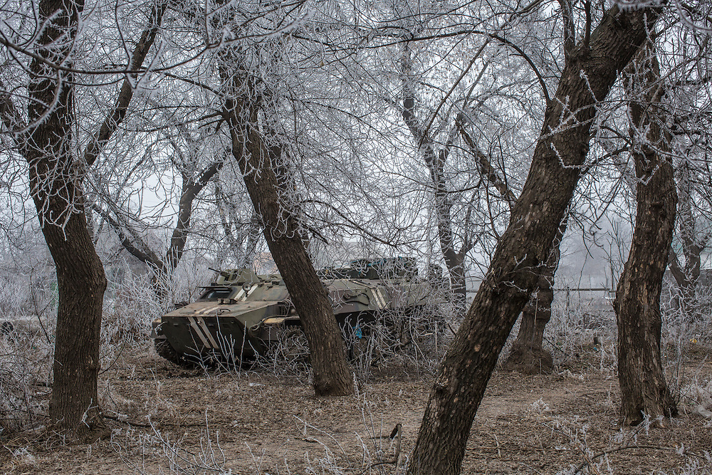 LUGANSKOYE, UKRAINE - FEBRUARY 15: A Ukrainian personnel carrier is parked among trees along the road to the embattled town of Debaltseve on February 15, 2015 in Luganskoye, Ukraine. A ceasefire scheduled to go into effect at midnight was reportedly observed along most of the front, save for near the embattled town of Debaltseve. (Photo by Brendan Hoffman/Getty Images) *** Local Caption ***