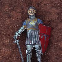 Scratched toy lead model of medieval knight in silver armour with open helmet carrying large red shield and long sword