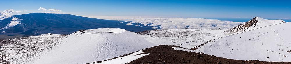 Panorama of winter snow on the summit of Mauna Kea, Big Island (Hawaii Island), Hawaii. Mauna Loa volcano is in the distance.