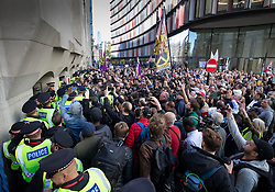 © Licensed to London News Pictures . 27/09/2018. London, UK. A crowd of supporters wait for former EDL leader Tommy Robinson to leave the Old Bailey, where his retrial for Contempt of Court was adjourned - following his actions outside Leeds Crown Court in May 2018 . Robinson was already serving a suspended sentence for the same offence when convicted in May and served time in jail as a consequence , but the newer conviction was quashed by the Court of Appeal and a retrial ordered . Photo credit: Peter Macdiarmid/LNP