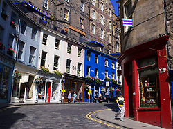View along historic West Bow street with colorful shops in old town district of Edinburgh Scotland