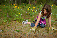 "JEROME A. POLLOS/Press..Savanna Routh, 10, pull weeds along a trail in Tuesday at Kiwanis Park in Post Falls. About 100 fifth-grade students from Ponderosa Elementary took part in the ""Take Pride in America"" program that encourages and recognizes efforts that promote taking pride by taking care of public lands."