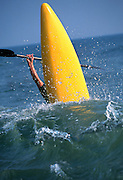 The nose of a yellow kayak launches above a wave during a surf competition in the Outer Banks of North Carolina.
