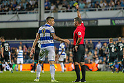 Referee Paul Tierney gives Queens Park Rangers forward Jordan Hugill (9) a yellow card pleads with after he stuck two fingers up at Assistant Referee Darren Cann (not in picture) after being flagged off-side during the EFL Sky Bet Championship match between Queens Park Rangers and Swansea City at the Kiyan Prince Foundation Stadium, London, England on 21 August 2019.