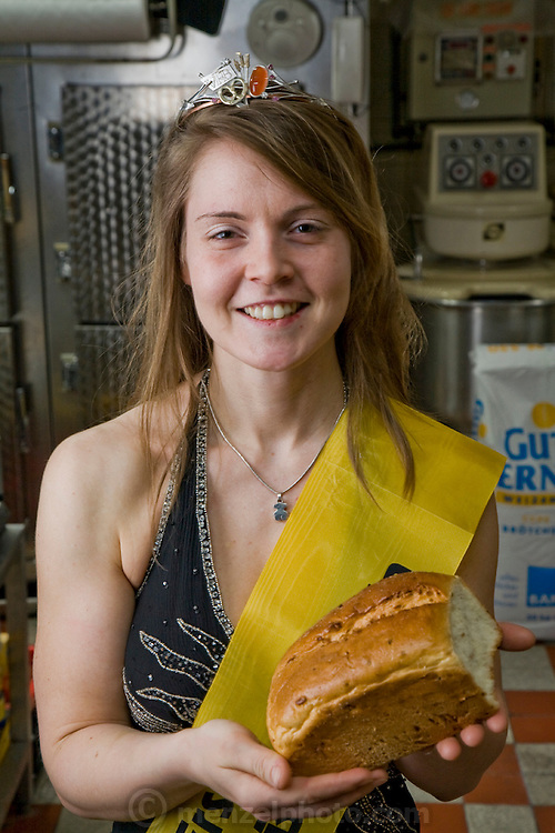 The Bread Queen Robina Weiser-Linnartz, a master baker and confectioner, holds a loaf of bread at her parent's bakery in Cologne, Germany.  (Robina Weiser-Linnartz is featured in the book What I Eat: Around the World in 80 Diets.) The caloric value of her day's worth of food in March was 3700 kcals. She is 28 years of age; 5 feet, 6 inches and 144 pounds. She's wearing her Bread Queen sash and crown, which she dons whenever she appears at festivals, trade shows, and educational events, representing the baker's guild of Germany's greater Cologne region. At the age of three, she started her career in her father's bakery, helping her parents with simple chores like sorting nuts. Her career plan is to return to this bakery, which has been in the family for four generations, in a few years. She will remodel the old premises slightly to allow customers the opportunity to watch the baking process, but plans to keep the old traditions of her forebears alive.   MODEL RELEASED.