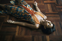 Chiang Mai, Thailand -- May 20, 2017: A woman rests on the floor of The Yoga Tree before a Dance Mandala class in Chiang Mai, Thailand.