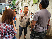 03 SEPTEMBER 2016 - BANGKOK, THAILAND: TAWATCHAI VORAMAHAKUN, center, a community historian and leader in the Pom Mahakan slum of the Pom Mahakan Fort talks to volunteers who came to support the residents of the fort. Hundreds of people from the Pom Mahakan community and other communities in Bangkok barricaded themselves in the Pom Mahakan Fort to prevent Bangkok officials from tearing down the homes in the community Saturday. The city had issued eviction notices and said they would reclaim the land in the historic fort from the community. People prevented the city workers from getting into the fort. After negotiations with community leaders, Bangkok officials were allowed to tear down 12 homes that had either been abandoned or whose owners had agreed to move. The remaining 44 families who live in the fort have vowed to stay.      PHOTO BY JACK KURTZ