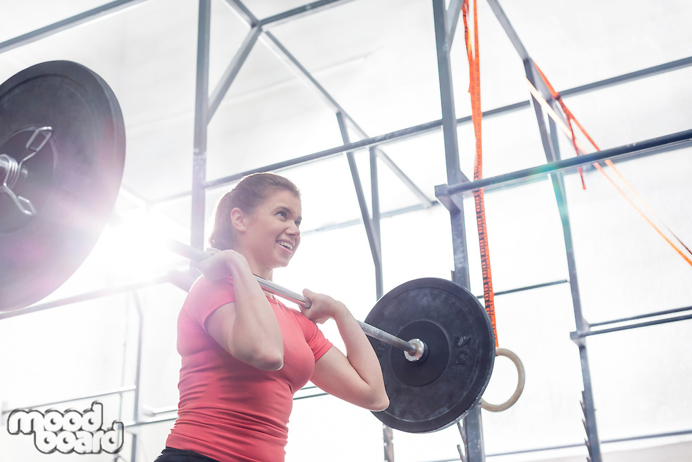 Low angle view of smiling woman lifting barbell in crossfit gym