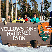 Clients pose for a photo on the top of the Yellowstone National Park entry sign.