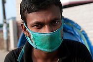 A rickshaw driver poses for a portrait in Ward 11 of Chittagong, Bangladesh. Many drivers wear full masks to guard themselves from the dust and fumes on the road.