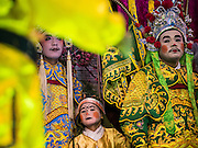 "14 MAY 2015 - BANGKOK, THAILAND: A Chinese opera performance at the Pek Leng Keng Mangkorn Khiew Shrine in the Khlong Toey slum in Bangkok. Chinese opera was once very popular in Thailand, where it is called ""Ngiew."" It is usually performed in the Teochew language. Millions of Chinese emigrated to Thailand (then Siam) in the 18th and 19th centuries and brought their culture with them. Recently the popularity of ngiew has faded as people turn to performances of opera on DVD or movies. There are still as many 30 Chinese opera troupes left in Bangkok and its environs. They are especially busy during Chinese New Year and Chinese holiday when they travel from Chinese temple to Chinese temple performing on stages they put up in streets near the temple, sometimes sleeping on hammocks they sling under their stage. Most of the Chinese operas from Bangkok travel to Malaysia for Ghost Month, leaving just a few to perform in Bangkok.       PHOTO BY JACK KURTZ"