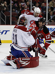Dec 16, 2009; Newark, NJ, USA; New Jersey Devils right wing Brian Rolston (12) is hit by Montreal Canadiens defenseman Roman Hamrlik (44) after a save by Montreal Canadiens goalie Carey Price (31) during the second period at the Prudential Center.