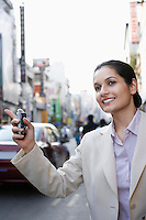 Business woman holding cell phone hailing taxi