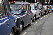 Black cabs of London line up waiting for a fare. Also know as Hackney carriage they provide a taxi service to the people in London.