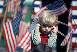 Americana Young boy holds covers ears from loud noise of passing small town holiday celebration parade.