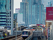 20 MAY 2015 - BANGKOK, THAILAND:  A Skytrain on the BTS Sukhumvit Line approaching Asok station. In 2013, the Bangkok Metropolitan Region consumed about 40 per cent of the Thailand's electricity, even though the BMR is only 1.5 per cent of the country's land area and about 22 per cent of its population. Most of the electricity consumed in Bangkok is generated in Laos and Myanmar.  PHOTO BY JACK KURTZ