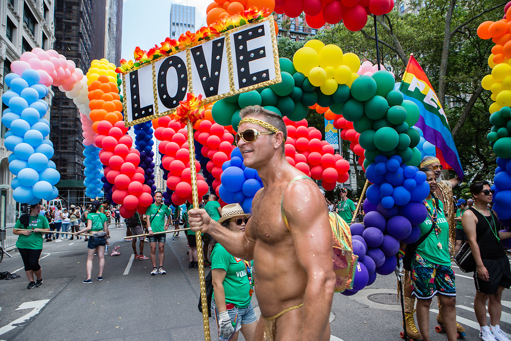 """New York, NY - 30 June 2019. The New York City Heritage of Pride March filled Fifth Avenue for hours with participants from the LGBTQ community and it's supporters. A man wearing a penis sheath and a headband carries a sign reading """"Love."""""""
