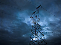 a high voltage transmission line stands against a cloudy sky in silhouette