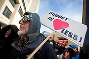 "MADISON, WI — FEBRUARY 13, 2015: Tim White holds a protest sign during the ""Stop the Cuts"" Rally on Library Mall, Saturday, February 14, 2015. The rally drew hundreds of student, faculty and community supporters in spite of the cold Midwest weather."