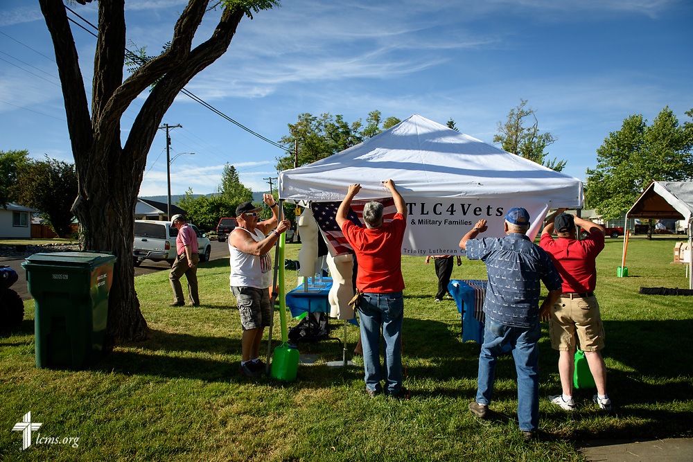 Paul Turpin (center), a veteran and church member at Trinity Lutheran Church, Grangeville, Idaho, works with fellow volunteers to erect the TLC4Vets outreach tent at the Grangeville Border Days Independence Day celebration and parade on Tuesday, July 4, 2017, in Grangeville. LCMS Communications/Erik M. Lunsford