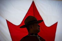 An RCMP officer is silhouetted against a Canadian flag during a special Canada Day citizenship ceremony in West Vancouver, B.C., on Saturday, July 1, 2017. Photo by Darryl Dyck/CP/ABACAPRESS.COM