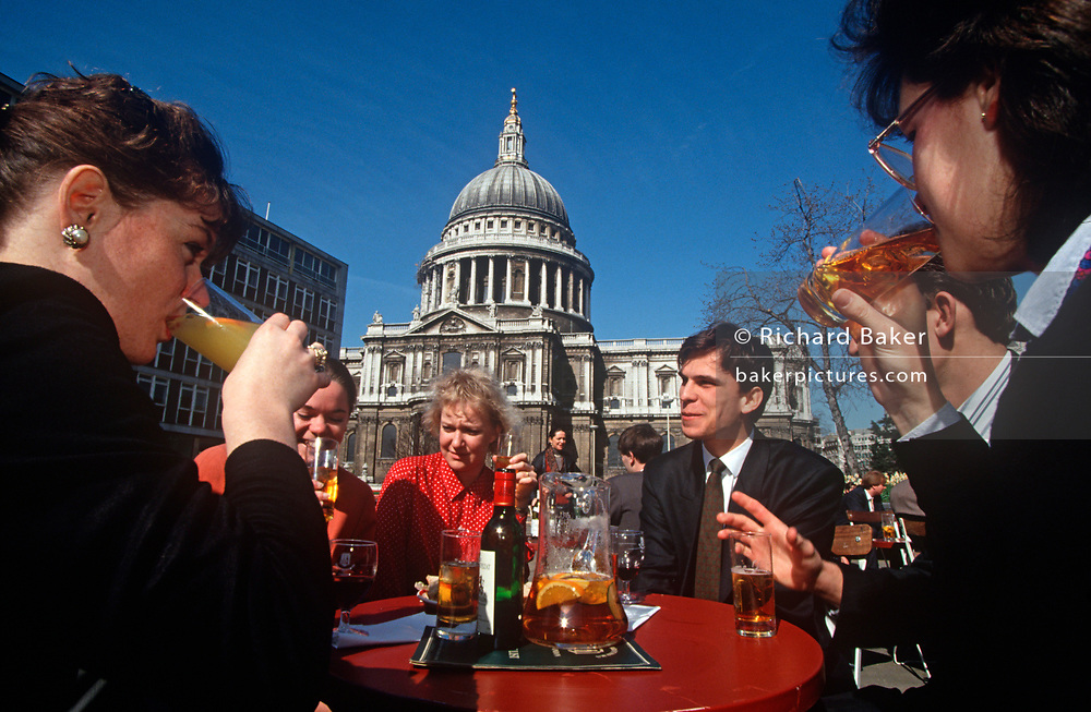 A group of 1990s work colleagues drink outside in summer sunshine, beneath the dome of St. Paul's Cathedral, in the City of London (aka The Square Mile), the capital's financial centre, on 20th June 1993, in London, England. (Photo by Richard Baker / In Pictures via Getty Images)