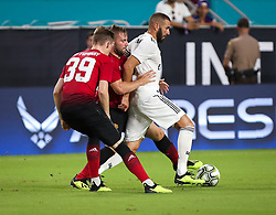 July 31, 2018 - Miami Gardens, Florida, USA - Real Madrid C.F. forward Karim Mostafa Benzema (9) drives the ball pressured by Manchester United F.C. midfielder Scott McTominay (39) and defender Luke Shaw (23) during an International Champions Cup match between Real Madrid C.F. and Manchester United F.C. at the Hard Rock Stadium in Miami Gardens, Florida. Manchester United F.C. won the game 2-1. (Credit Image: © Mario Houben via ZUMA Wire)