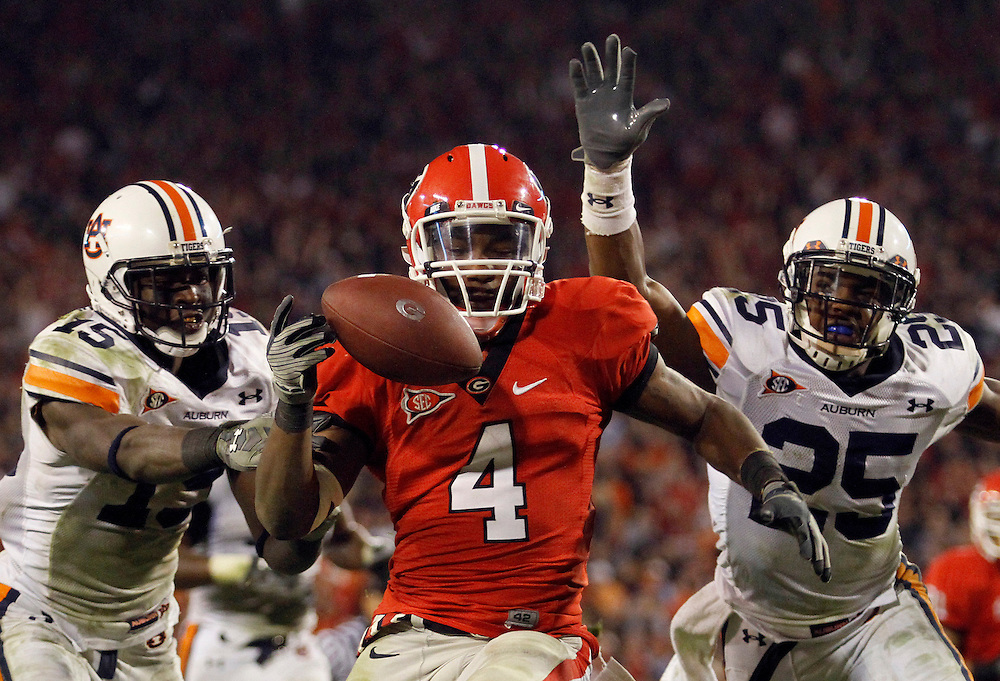 Auburn's Neiko Thorpe, left, and Daren Bates attempt to stop Georgia's Caleb King from scoring the game winning touchdown fduring the Bulldogs 31-24 victory over the Auburn Tigers at Sanford Stadium in Athens, Ga. on Saturday, Nov. 14, 2009.