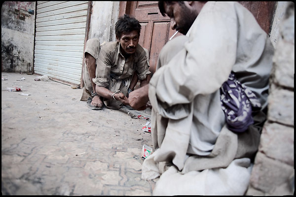 """Khalid (left) and Safir Alì (right), 27 and 28 years old, both homeless heroin addicts by 6 years, are sharing dose of drug. For daily consume of """"white powder"""", must beg around the area where they usually live. Shan Nazar Kapull, Rawalpindi, Pakistan, on friday, August 29 2008.....""""Pakistan is one of the countries hardest hits by the narcotics abuse into the world, during the last years it is facing a dramatic crisis as it regards the heroin consumption. The Unodc (United Nations Office on Drugs and Crime) has reported a conspicuous decline in heroin production in Southeast Asia, while damage to a big expansion in Southwest Asia. Pakistan falls under the Golden Crescent, which is one of the two major illicit opium producing centres in Asia, situated in the mountain area at the borderline between Iran, Afghanistan and Pakistan itself. .During the last 20 years drug trafficking is flourishing in the Country. It is the key transit point for Afghan drugs, including heroin, opium, morphine, and hashish, bound for Western countries, the Arab states of the Persian Gulf and Africa..Hashish and heroin seem to be the preferred drugs prevalence among males in the age bracket of 15-45 years, women comprise only 3%. More then 5% of whole country's population (constituted by around 170 milion individuals),  are regular heroin users, this abuse is conspicuous as more of an urban phenomenon. The substance is usually smoked or the smoke is inhaled, while small number of injection cases have begun to emerge in some few areas..Statistics say, drug addicts have six years of education. Heroin has been identified as the drug predominantly responsible for creating unrest in the society."""""""