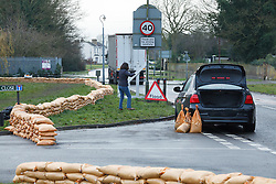 © Licensed to London News Pictures. 10/02/2014. Datchet, Berkshire, UK. A woman taking sandbags from a constructed flood defence, leaving residents angry. Flooding in Datchet today, 10th February 2014 after the River Thames burst its banks. Photo credit : Rob Arnold/LNP