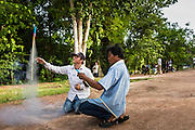 28 JUNE 2014 - DAN SAI, LOEI, THAILAND:  Men launch a small rocket during the Ghost Festival in Dan Sai. The rocket launches are a northern Thai tradition. They're thought to ensure a bountiful rainy season. Phi Ta Khon (also spelled Pee Ta Khon) is the Ghost Festival. Over three days, the town's residents invite protection from Phra U-pakut, the spirit that lives in the Mun River, which runs through Dan Sai. People in the town and surrounding villages wear costumes made of patchwork and ornate masks and are thought be ghosts who were awoken from the dead when Vessantra Jataka (one of the Buddhas) came out of the forest.   PHOTO BY JACK KURTZ