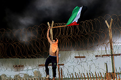 October 8, 2018 - Beit Lahia, Gaza Strip, Palestinian Territory - A protestor climbs the border fence waving a palestinian flag. Gaza's Health Ministry says 11 Palestinians have been wounded by Israeli gunfire in a protest along the territory's land and sea boundary with Israel. Monday's beach demonstration was part of a half-year-long protest campaign by Gaza's Hamas rulers. Protesters on fishing boats fixed Palestinian flags on a fence that extends into the Mediterranean. On land, other protesters briefly breached the frontier under the cover of smoke from flaming tires. Israeli soldiers responded with tear gas and live fire. (Credit Image: © Mahmoud Khattab/APA Images via ZUMA Wire)