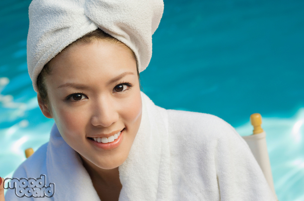 Young woman wearing bathrobe by swimming pool, portrait