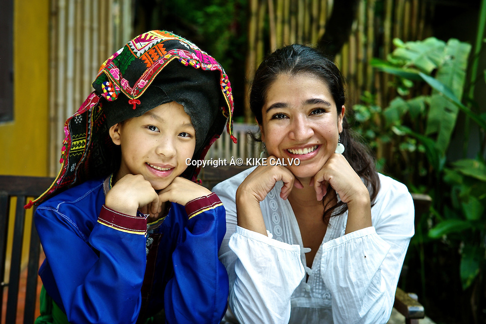 Tourist posing with a teen girl wearing Tai Dam traditional dress in Laos. Its used in Luang Prabang province.
