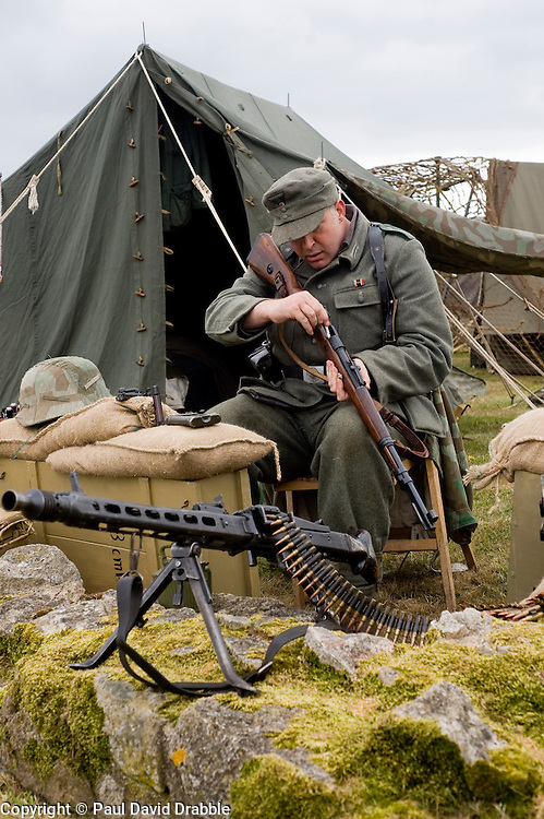 A reenactor from the Northern World War Two Association portraying life in the field for a German Soldier with the 21st Panzer Division as he sits cleaning a Bolt action Mauser K98 rifle. In the foreground is an MG42 machine gun.<br /> Scarborough Castle<br /> Sunday 30th May 2010<br /> Image &copy; Paul David Drabble