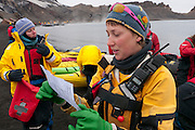 Deception Island, off the Antarctic Peninsula.  organizing the kayaks to be launched near Pendulum Cove's thermal waters in Whaler's Bay, a protected harbor. Deception Island is the site of a circular flooded volcanic caldera. Conditions had to be perfect in order to kayak outside of the Bay, and they were. On the shore are rusting remains of Whaling operations (1911 to 1931) and the ruins of a WWII British base, Port Foster (1944-1967). Evacuated after a volcanic eruption, then closed permanently in 1969 after another eruption. Chinstrap penguins in the steam of the volcanics that are still warming the beach sand at Whaler's Bay.