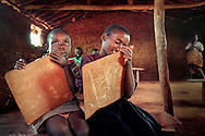 Bitama sits in silence while her classmates practice writing the Kinyarwanda alphabet in their elementary school classroom at the Mkugwa refugee camp. Bitama was so young at the time of her parents' death that there is little information on her origins. Having experienced so much loss at such a young age, she is often silent and expressionless.