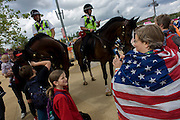 American spectators admire mounted police officers on horseback help control crowds and provide security in the Olympic Park during the London 2012 Olympics. This land was transformed to become a 2.5 Sq Km sporting complex, once industrial businesses and now the venue of eight venues including the main arena, Aquatics Centre and Velodrome plus the athletes' Olympic Village. After the Olympics, the park is to be known as Queen Elizabeth Olympic Park.